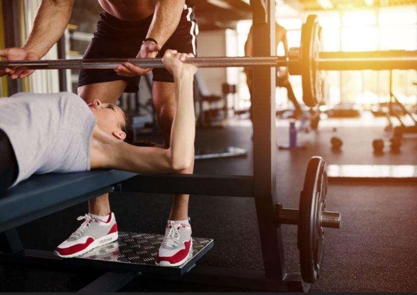 Chica haciendo pesas en el gimnasio.