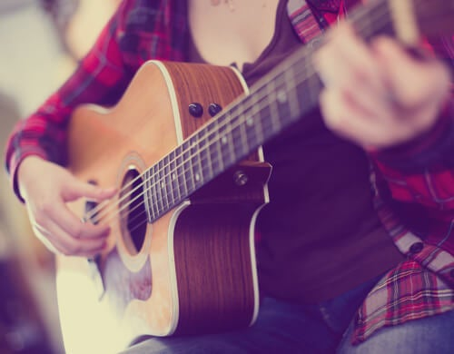 Chica tocando la guitarra.