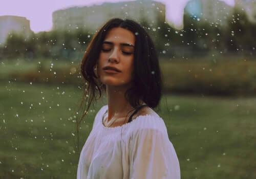 Mujer con los ojos cerrados en el campo.