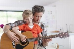 Padre e hijo en el momento de aprender a tocar la guitarra