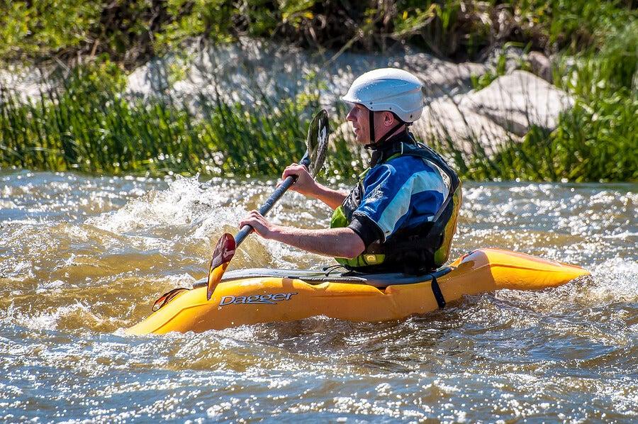 Deportista practicando piragüismo en aguas bravas