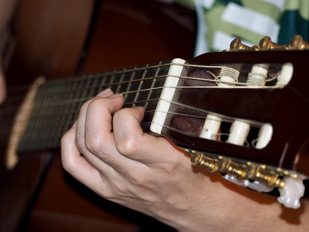 Guitarrista ejecutando el golpe de una pulgada