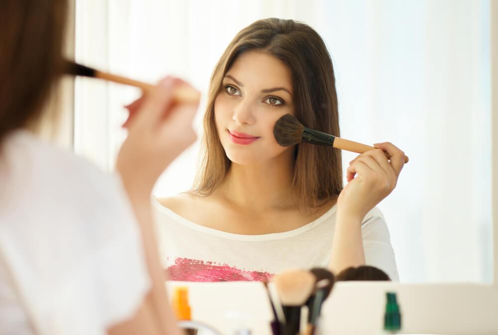 Mujer aplicándose colorete
