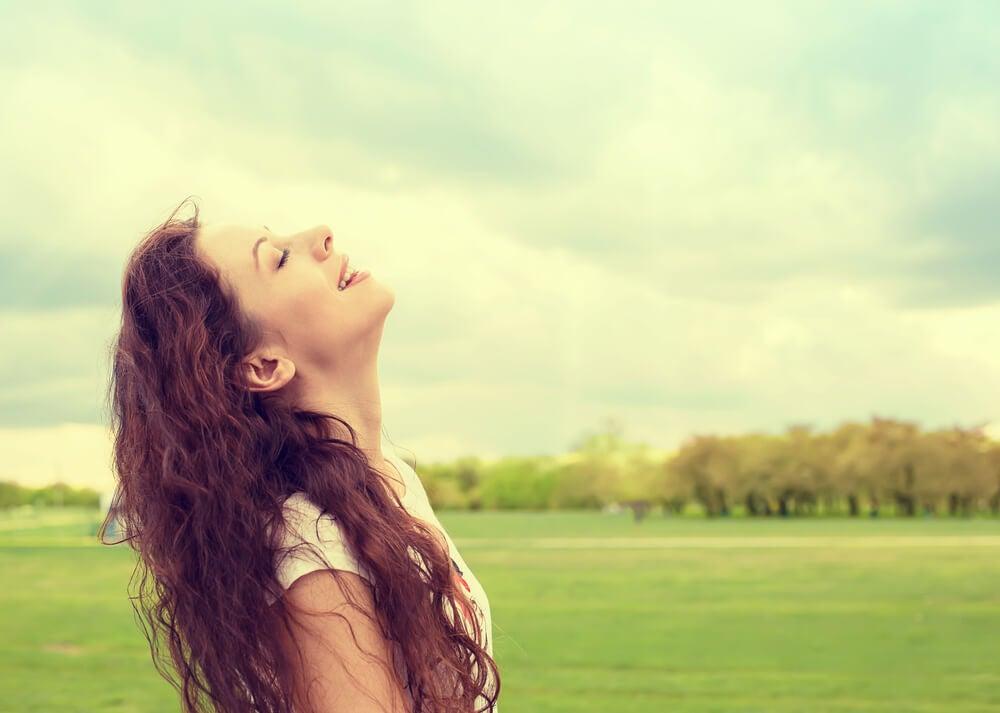 Mujer feliz que ha sacado piedras de su mochila emocional