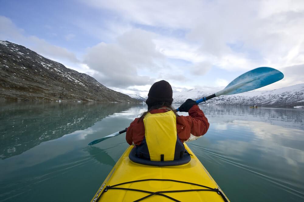 Hombre practicando piragüismo en invierno