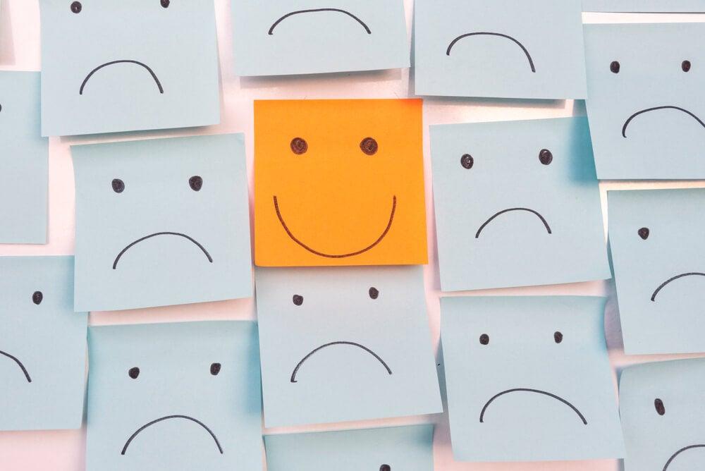 Papel con una cara sonriente entre caras tristes