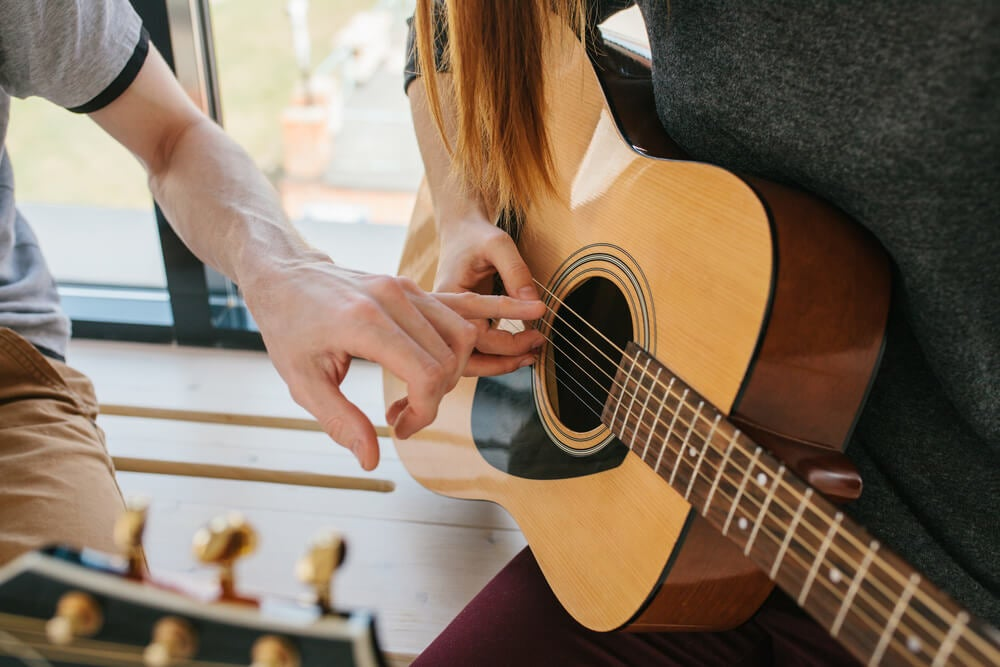 Profesor enseñando a tocar mejor la guitarra