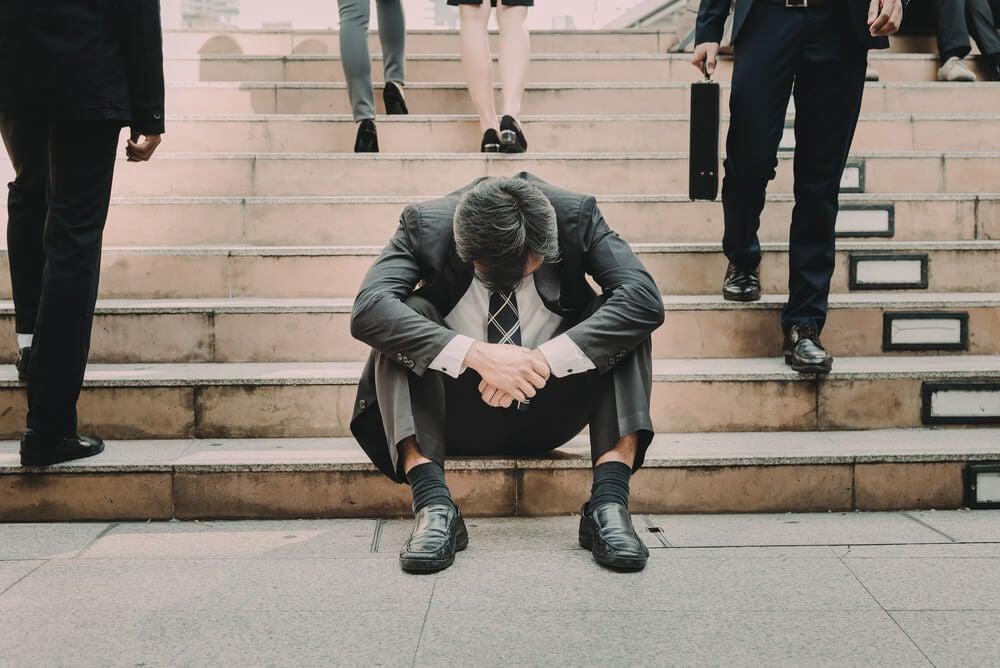 Hombre con miedo al fracaso y la cabeza agachada