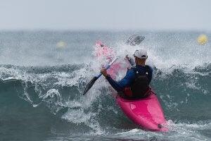 Hombre toma una ola haciendo kayak surf.