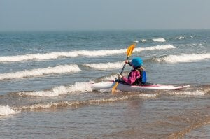 Una mujer se dirige hacia el mar para tomar una ola.