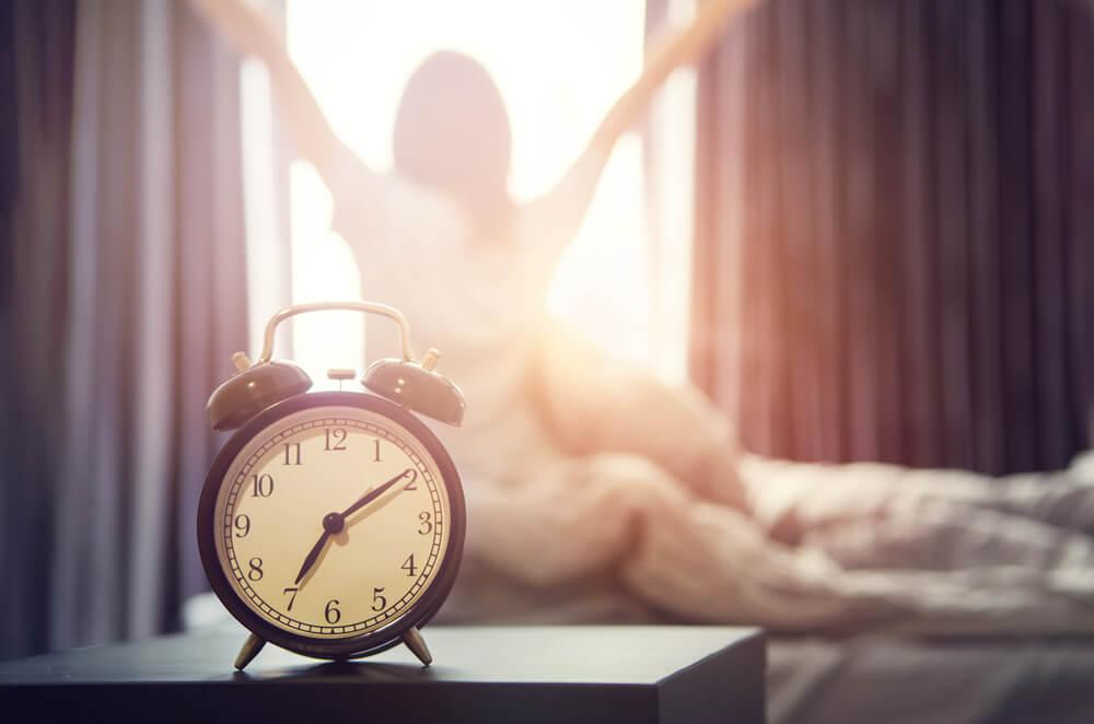 Mujer levantándose pronto, uno de los hábitos diarios saludables